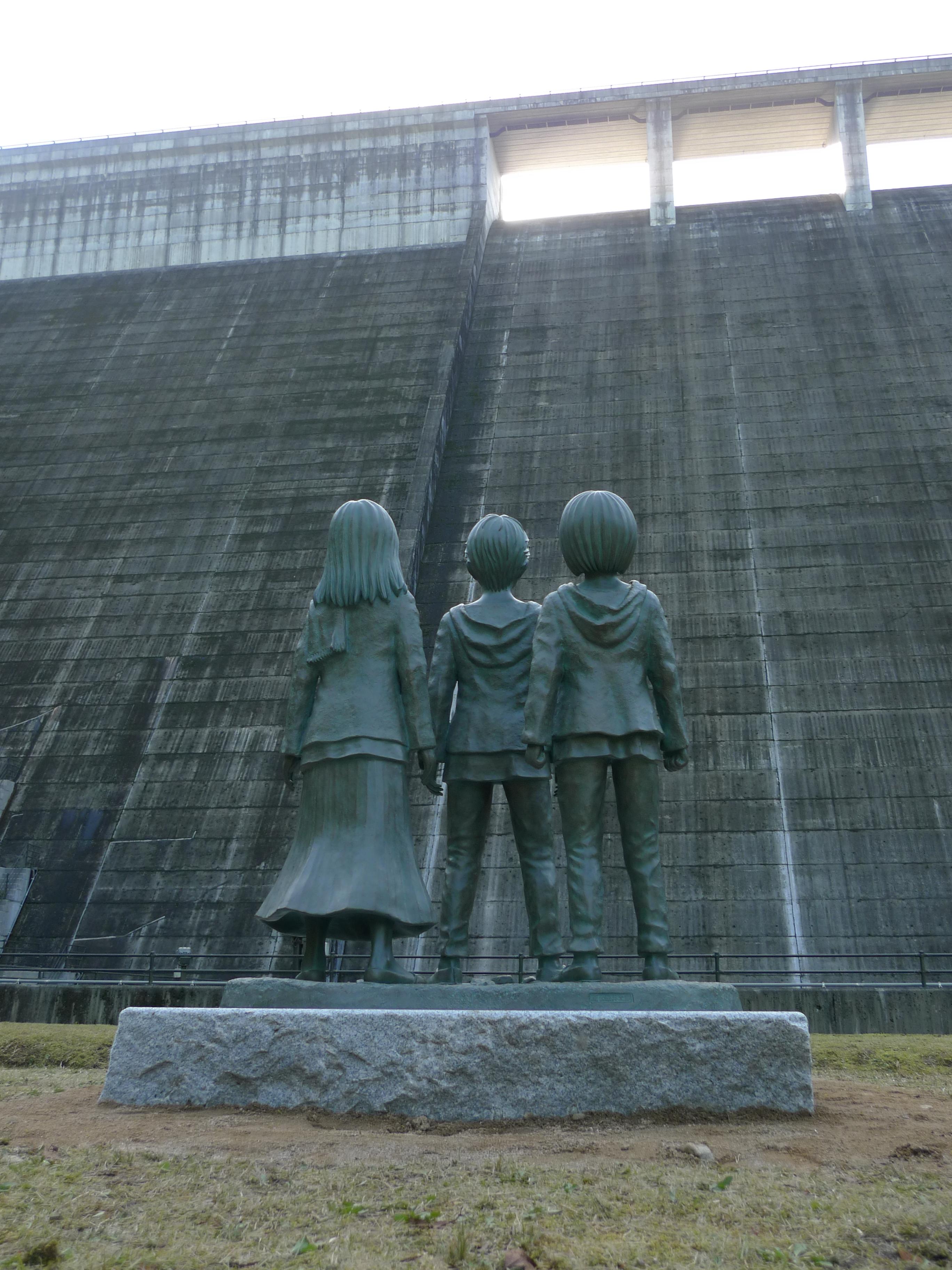 大山ダム堤体を見上げるエレン・ミカサ・アルミンの銅像(背面)